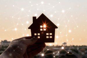 Protección de datos comunidad de propietarios - Persona sosteniendo figura de edificio