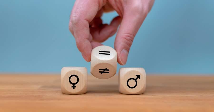 Comisión negociadora plan de igualdad: Mano da un dado y cambia un signo desigual a un signo igual simbolizando la igualdad de género